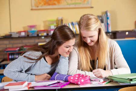 Two teenage schoolgirls in classroom having fun together photo
