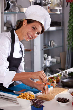Laughing female chef preparing a small amuse on a stick photo