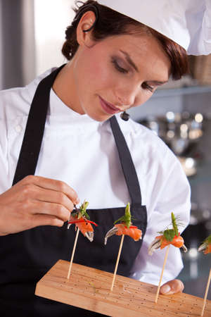 Female chef giving a cooking demonstration adding a drop of balsamico to her dish photo