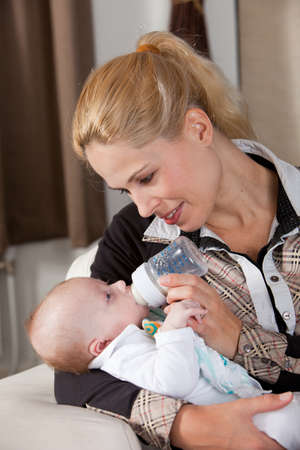 Beautiful mother feeding her newborn baby with a bottle of milk photo