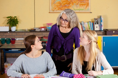 Teacher standing behind the desk of her two students in classroom Stock Photo - 9007754