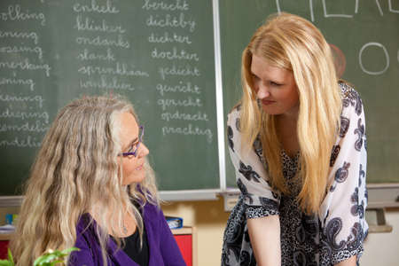 Teacher and a student in the classroom having a conversation Stock Photo - 9007840