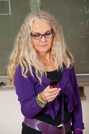 Mature teacher standing in the classroom sending a text message photo