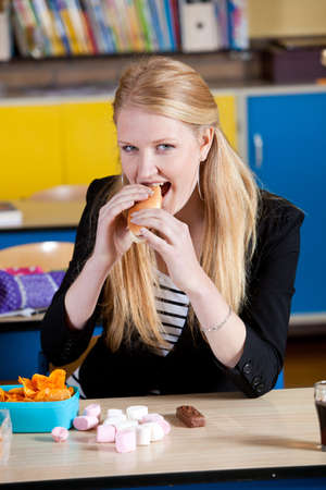Schoolgirl eating a very unhealthy lunch with hotdog and marshmallows photo