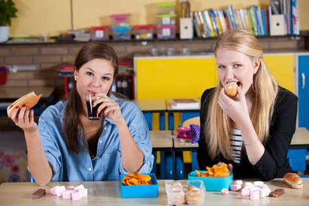 Two schoolgirls eating a very unhealthy lunch at their desks photo
