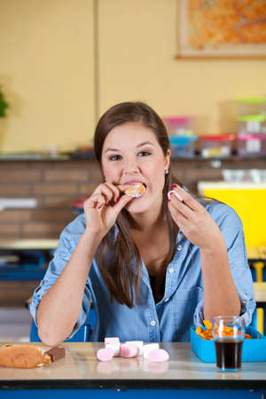 Pretty schoolgirl filling herself with unhealthy food photo