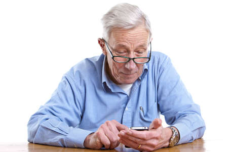 Senior man pulling a face while holding a mobile Stock Photo - 11112704