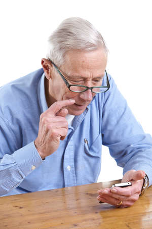 Senior man with mobile looking puzzled Stock Photo