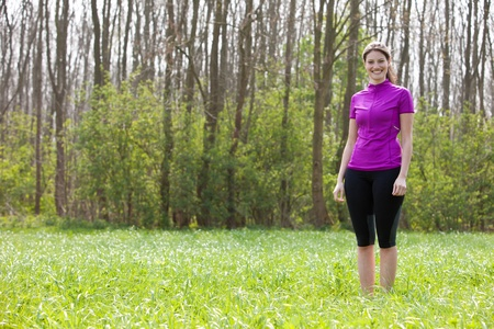 Beautiful fit girl standing in the meadow wearing sportsclothes photo
