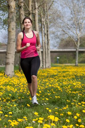 Beautiful young girl running in a field of dandelions Stock Photo - 11112700