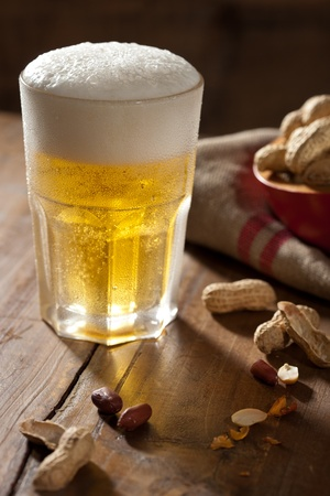 Cool glass of beer with a snack next to it Stock Photo - 11112715
