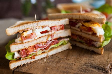 Vers gemaakte clubsandwiches geserveerd op een houten snijplank Stockfoto
