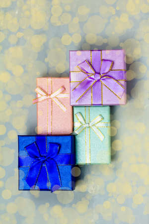 Purple, pink, blue gift box with blue bokeh background. Holiday greeting card. Christmas, new year, birthday. Space for text
