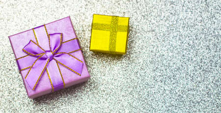 Purple and gold gift box with grey bokeh background. Holiday greeting card. Christmas, new year, birthday. Space for text Stock Photo