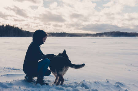 Girl with a dog on the shore of a winter lake. A dog is a man s best friend, and in winter a dog can warm up in any conditions.