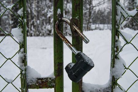 Open padlock on the old fence. Snow-covered fence. Фото со стока