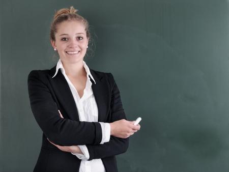 Pretty smiling teacher at the blackboard