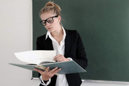 Portrait of young teacher with book and eyeglasses looking at camera by the blackboard  photo