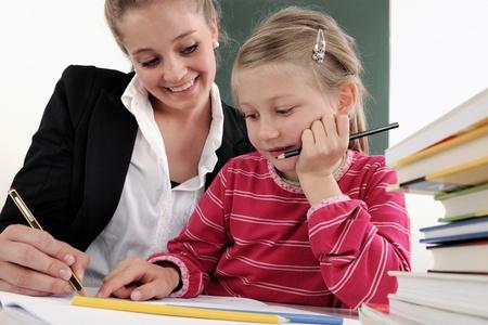 Teacher helping student at her desk in elementary school classroom.