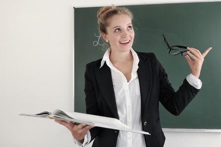 Cheerful female teacher holding a book in a maths classroom