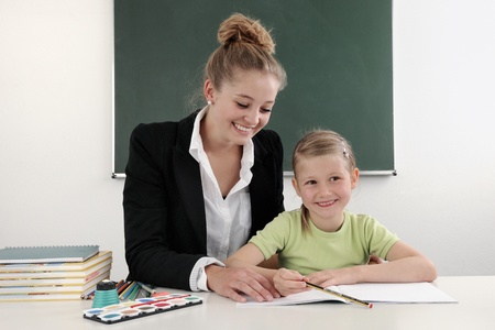 Teacher helping student in classroom photo