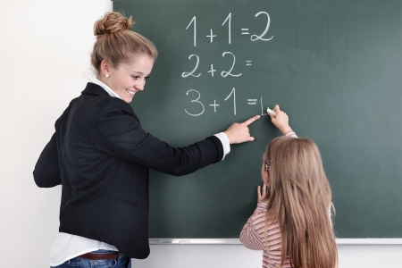 Teacher watching young female student write on blackboard. Horizontally framed shot.  Standard-Bild