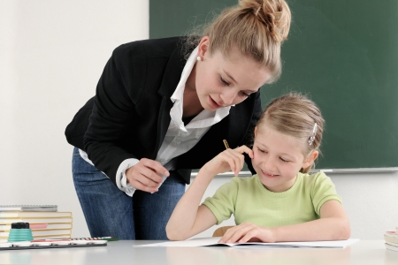 Teacher with pupil writing in a classroom