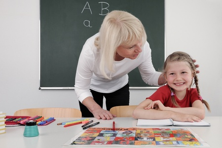 teacher teaching 6 year old student in classroom