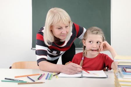 Teacher helping elementary school child with written project
