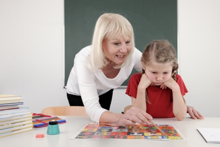 Teacher Helping Child in Classroom photo