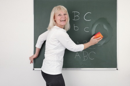 the elderly tutor: Teacher cleaning the chalkboard, suits horizontal composition  Stock Photo