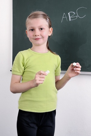 learning by doing: Portrait of smart school child standing at blackboard and looking at camera Stock Photo