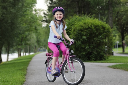 child s: Young girl on bicycle outdoors smiling