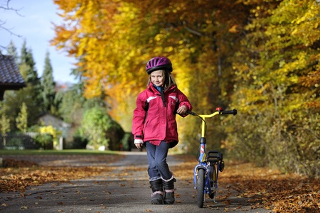 Cheerful preschool girl riding scooter  photo