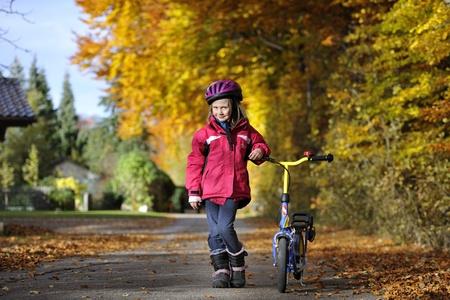 Cheerful preschool girl riding scooter