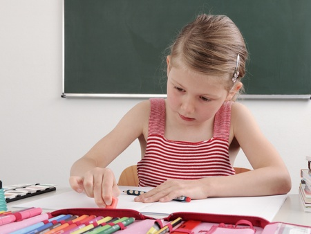 schooling: schoolchild in classroom near blackboard Stock Photo