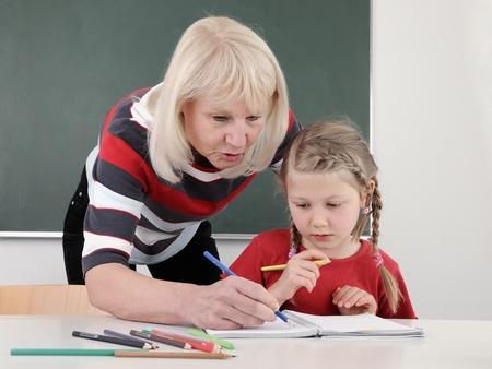 tutor: Maestro de escuela primaria ayudando a alumno con lectura  Foto de archivo