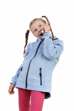 Little girl speaking by cell phone, white background  photo