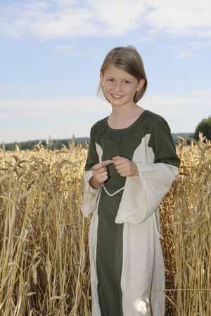 Girl in field picking stalks of wheat, smiling Standard-Bild
