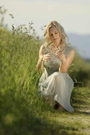 Young blonde woman sitting in the field
