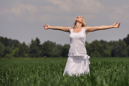 Woman standing in a meadow with arms reaching out photo