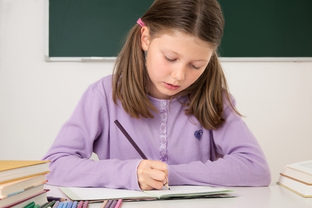 Female pupil working at a desk in the classroom Standard-Bild