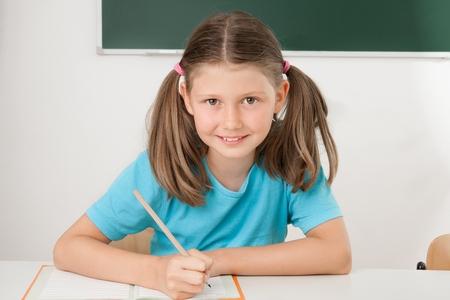 escuela primaria: Estudiante femenino con lecciones en la escuela