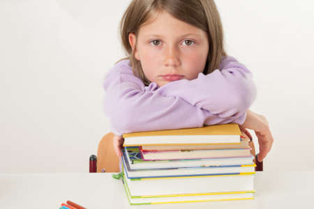 Female pupil leaning on a pile of books Standard-Bild