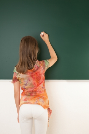 Female student writing on the black board