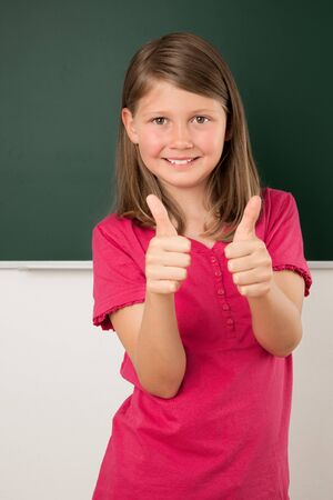 Female pupil holds thumbs up