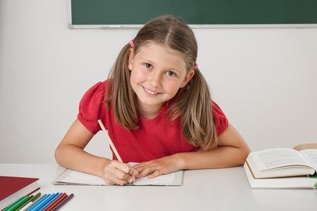 Female pupil writing at a desk at school Standard-Bild