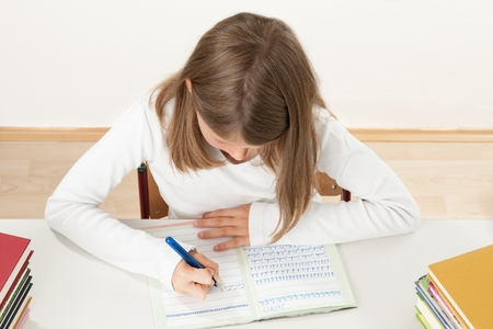 Female pupil writing at a desk at school Stock Photo