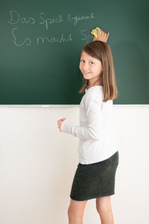 Smiling schoolgirl writing on the blackboard