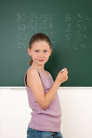 Smiling Schoolgirl standing in front of the blackboard Standard-Bild